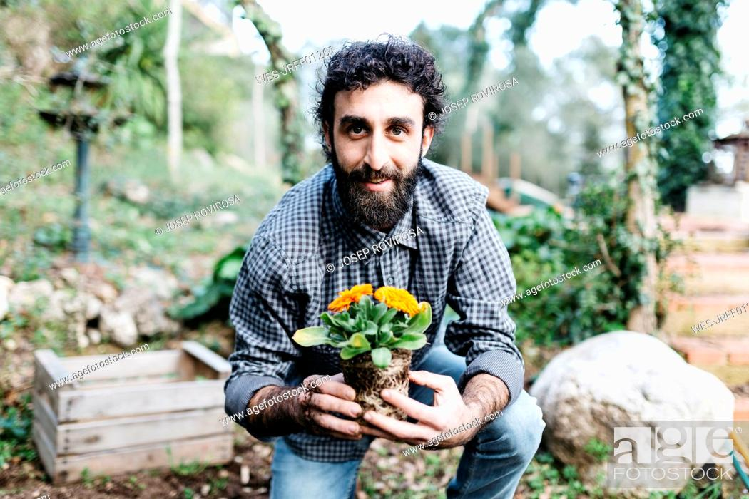 Stock Photo: Smiling gardener holding a flower.