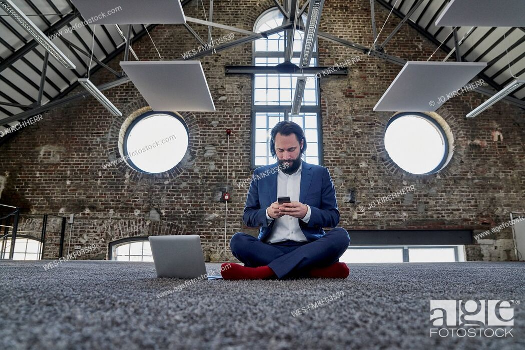 Stock Photo: Businessman sitting on carpet in a loft using cell phone.