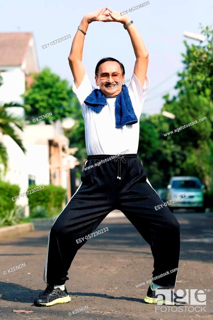 Stock Photo: Portrait of senior man exercising on street.