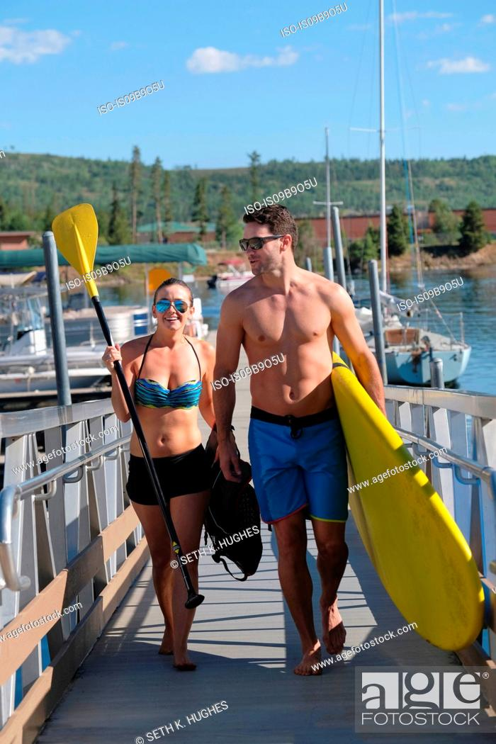 Stock Photo: Paddleboarding couple carrying paddleboard on lake pier, Frisco, Colorado, USA.
