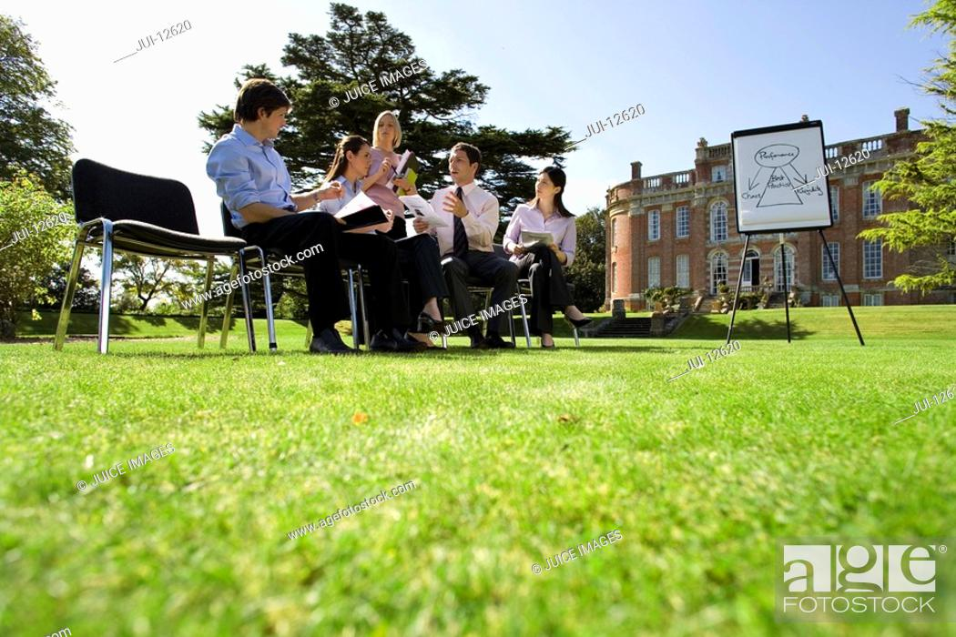Stock Photo: Businessmen and women with folders in training course by manor house, ground view.