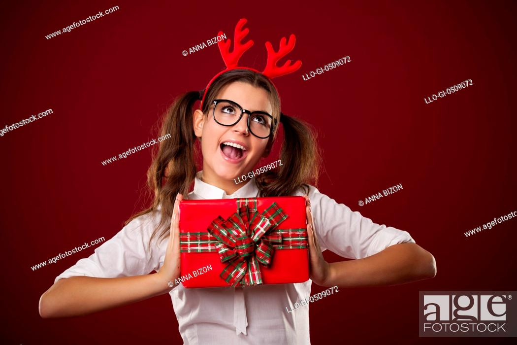 Stock Photo: Nerdy woman holding red Christmas present Debica, Poland.