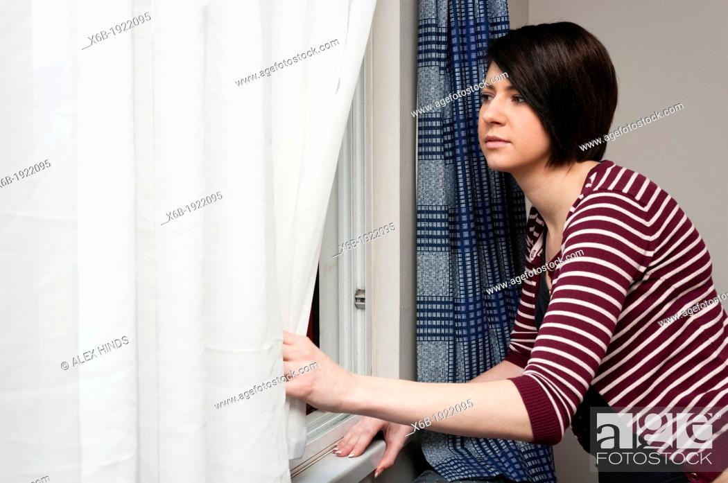 Stock Photo: Young woman looking out of window.