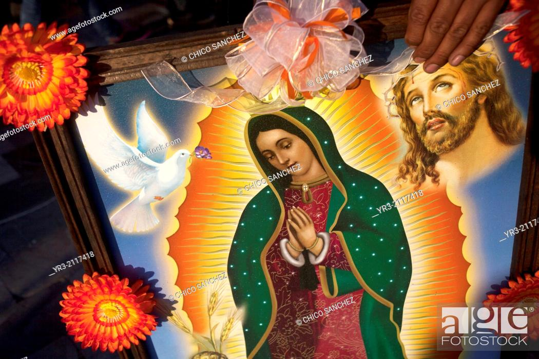 Stock Photo: A woman holds a picture of the Virgin of Guadalupe decorated with flowers at the pilgrimage to Our Lady of Guadalupe Basilica in Mexico City, Mexico.