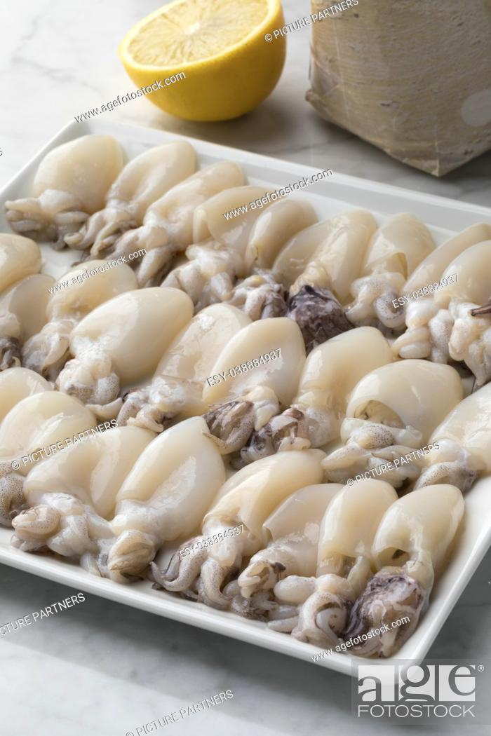 Photo de stock: Fresh cleaned raw baby squid on a dish.