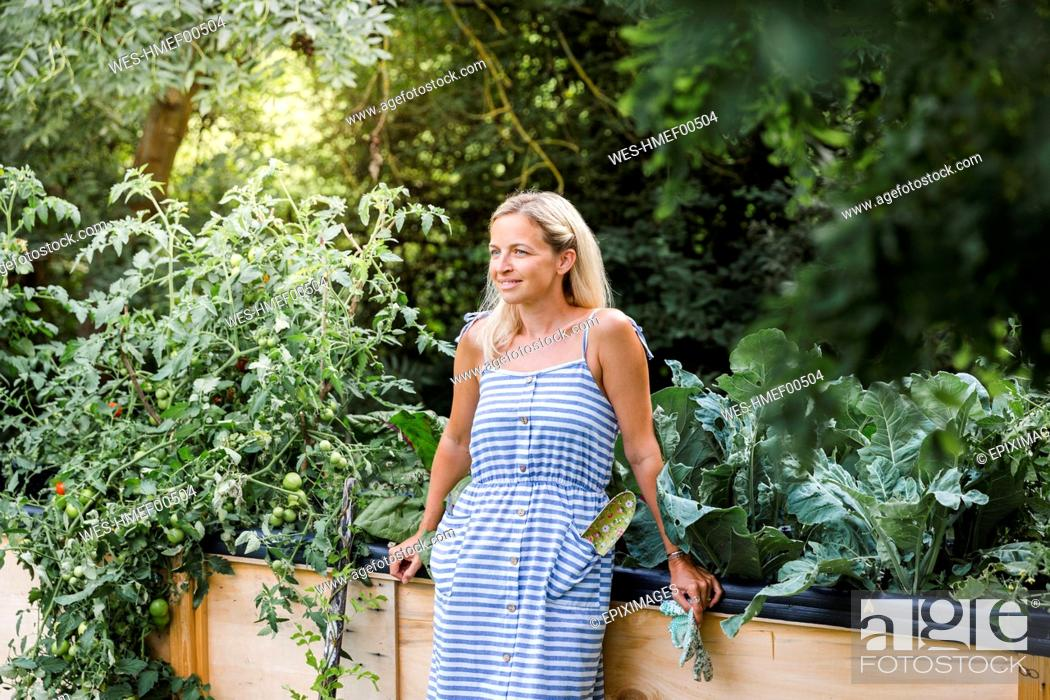 Stock Photo: Blond woman standing in front of her raised bed in her own garden.