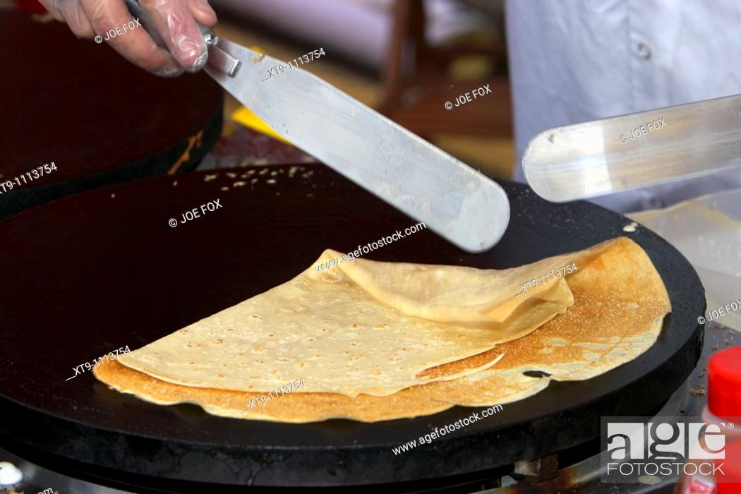 Stock Photo: man making crepe pancakes on a fast food stall in a market Holywood County Down Northern Ireland UK.