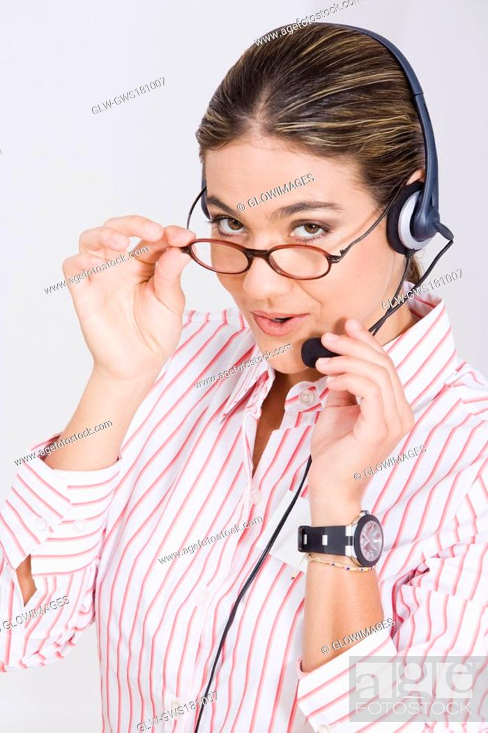 Stock Photo: Portrait of a businesswoman adjusting her eyeglasses and a headset.