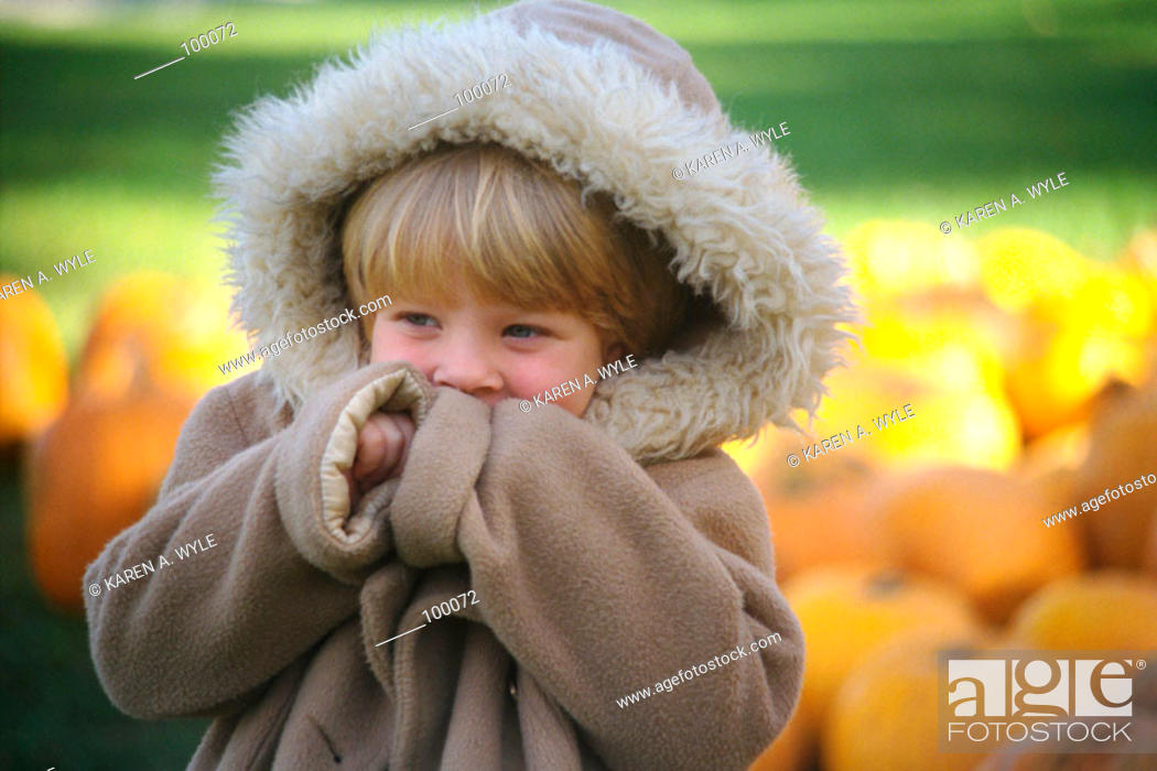 Stock Photo: Young girl in oversized warm parka near pile of pumpkins.