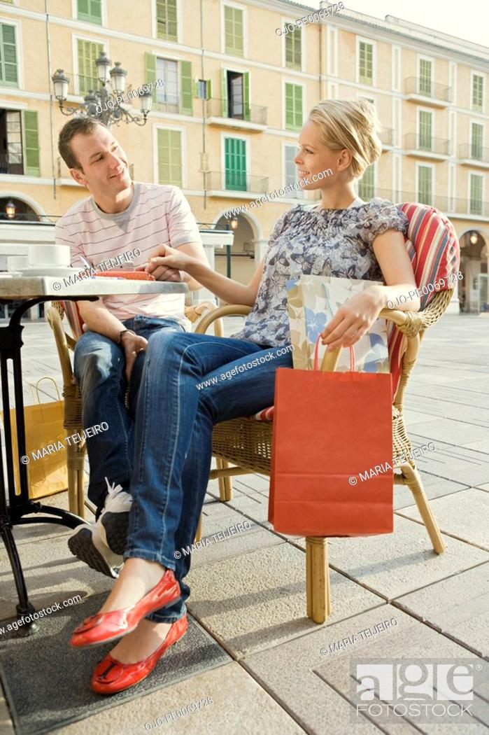 Stock Photo: Man and woman at outdoor cafe holding shopping bag.