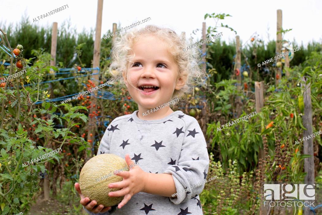 Imagen: Little girl with cantaloupe in garden.