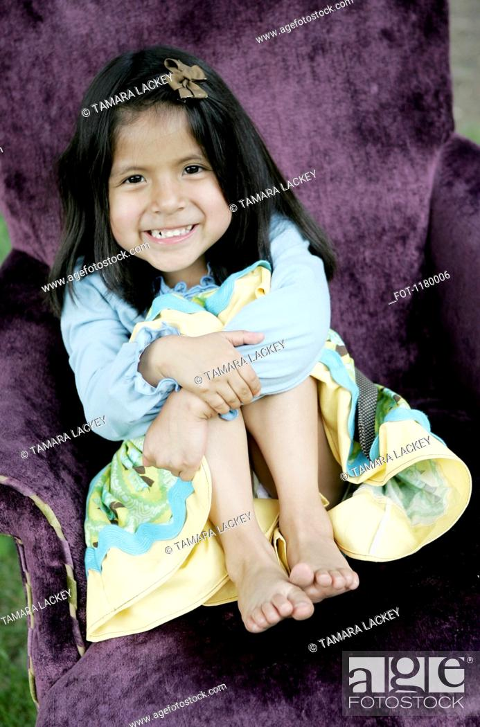 Stock Photo: A young smiling girl sitting in a purple armchair.