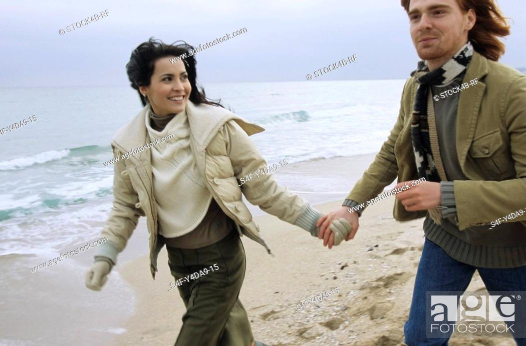 Stock Photo: Young brownhaired Woman going for a Walk at the Beach with her Boyfriend - Happiness - Togetherness - Holiday - Season - Winter.