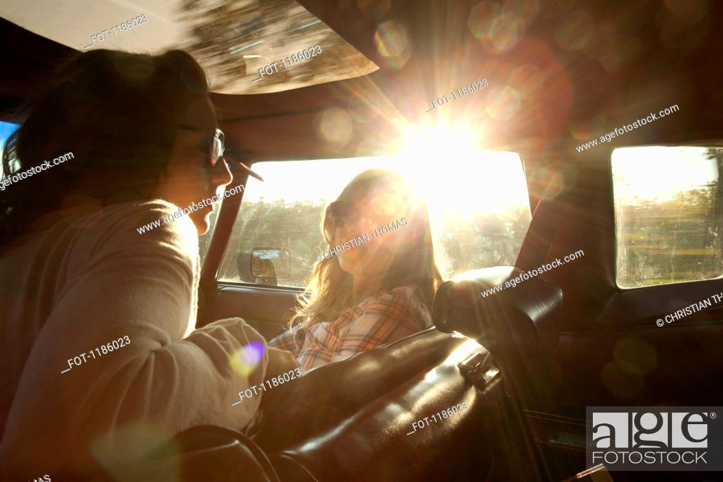 Stock Photo: Two serene rockabilly women in the front seat of a vintage car.