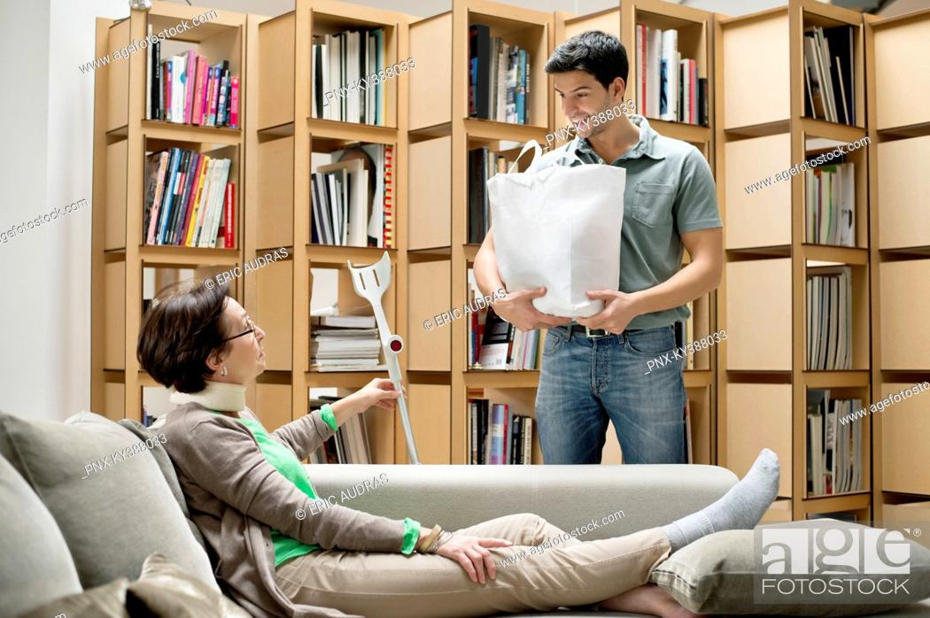 Stock Photo: Man talking to his mother reclining on a couch.