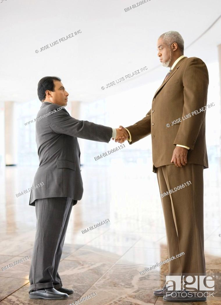 Stock Photo: Tall businessman shaking hands with short businessman.