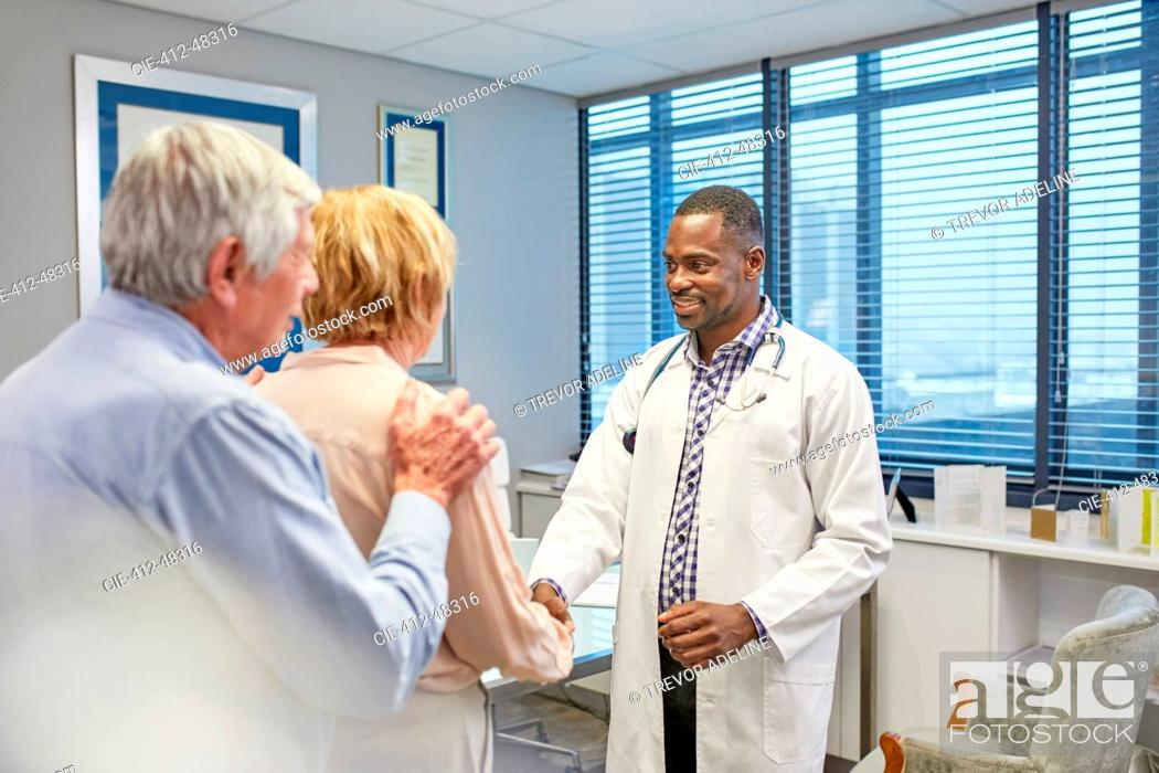 Stock Photo: Doctor shaking hands with senior couple in doctors office.