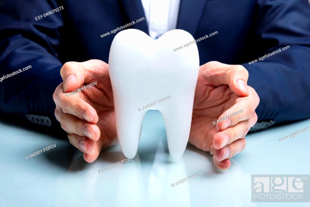 Stock Photo: Man's Hand Protecting Healthy Hygienic White Tooth On Reflective Table.