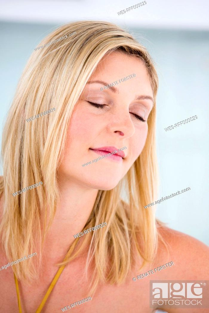 Stock Photo: Germany, Mid adult woman relaxing with eyes closed.