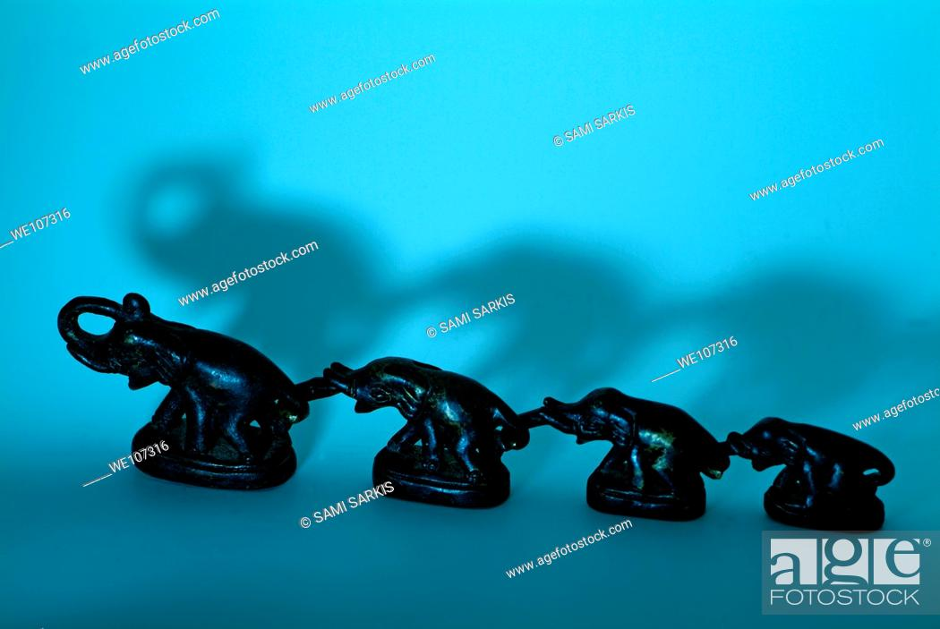 Stock Photo: Row of elephant ornaments attached by their trunks.