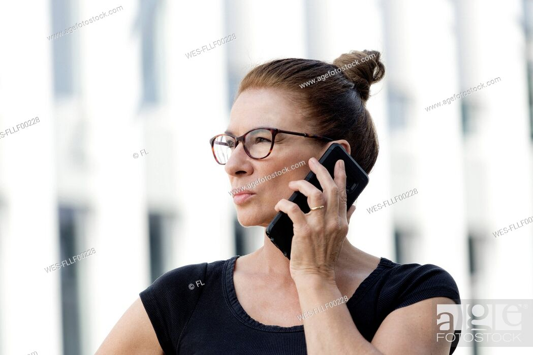 Stock Photo: Portrait of woman on cell phone outdoors.