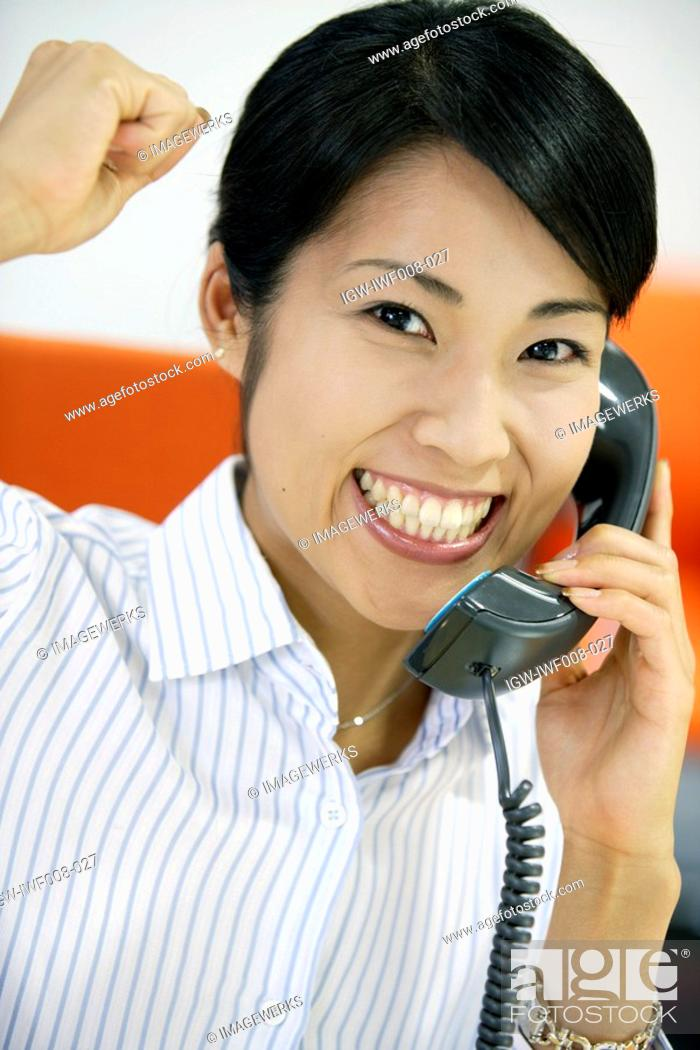 Stock Photo: An ecstatic woman showing her emotions while conversing on the telephone,.