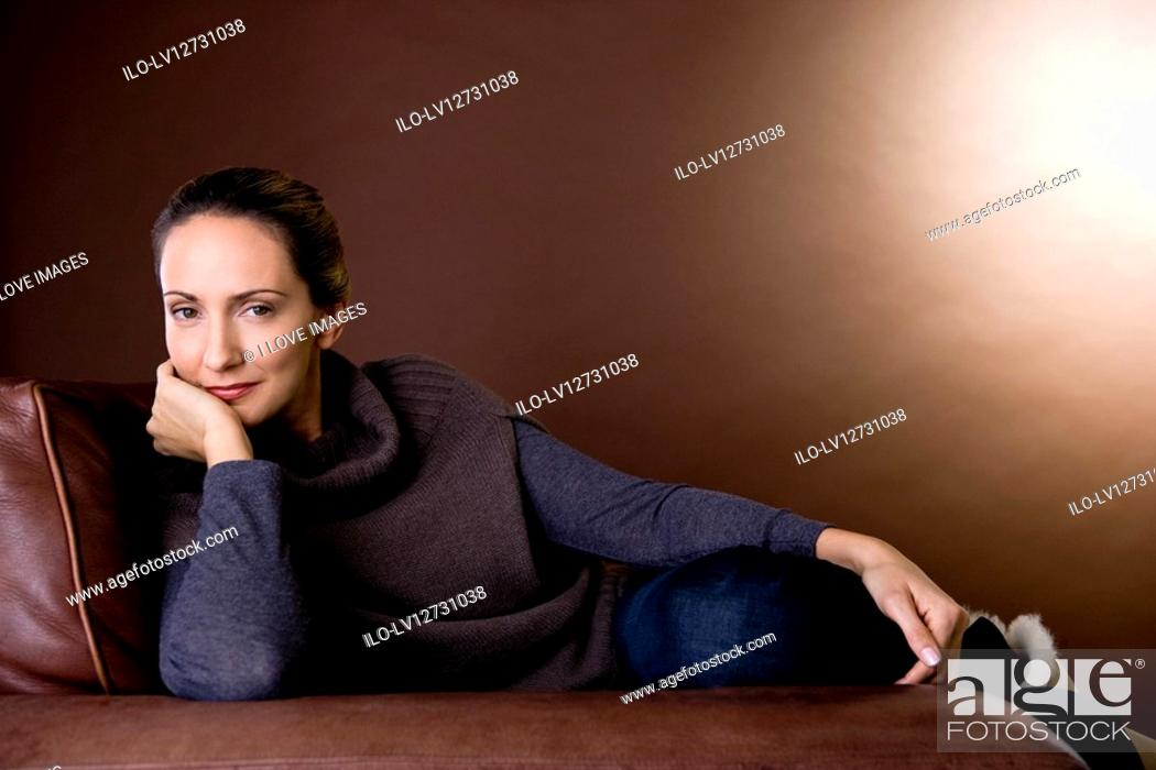 Stock Photo: A mid adult woman sitting in an armchair.