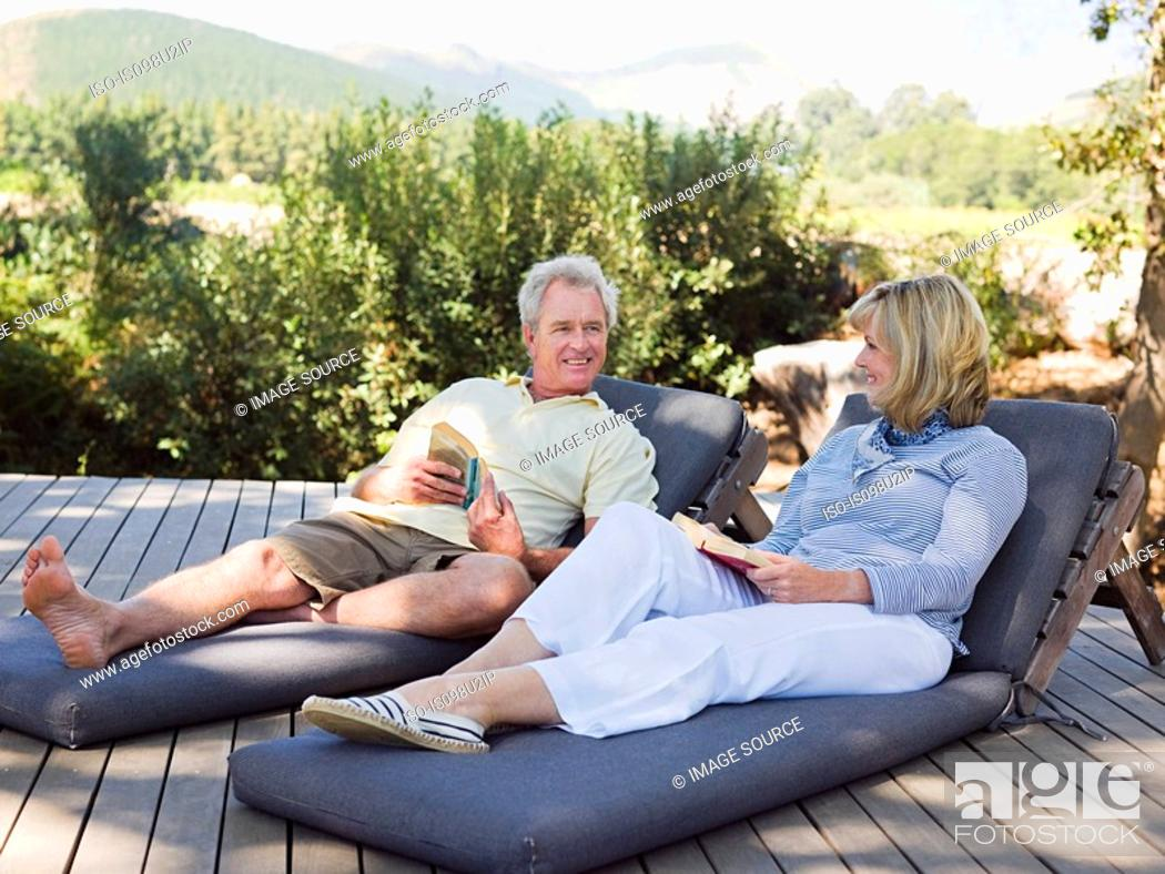 Stock Photo: Mature couple relaxing on loungers with books.