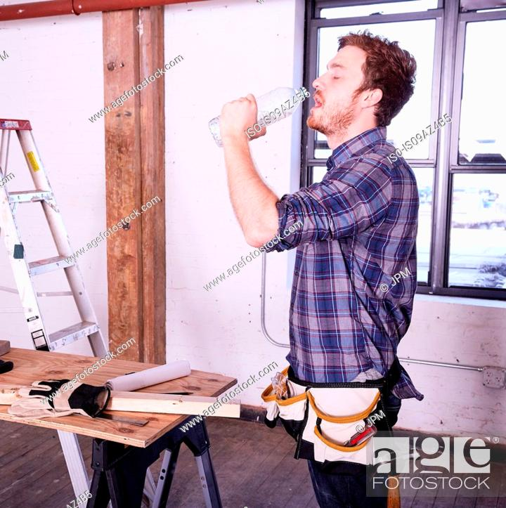 Stock Photo: Carpenter in workshop drinking from water bottle.