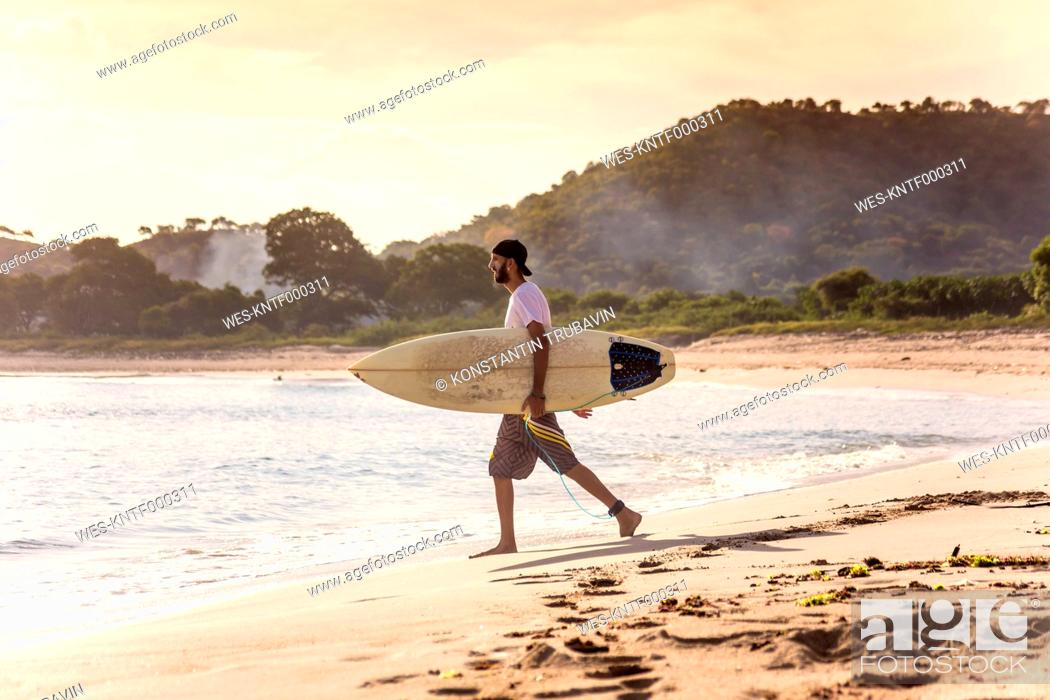 Stock Photo: Indonesia, Sumbawa island, Surfer on a beach in the evening.