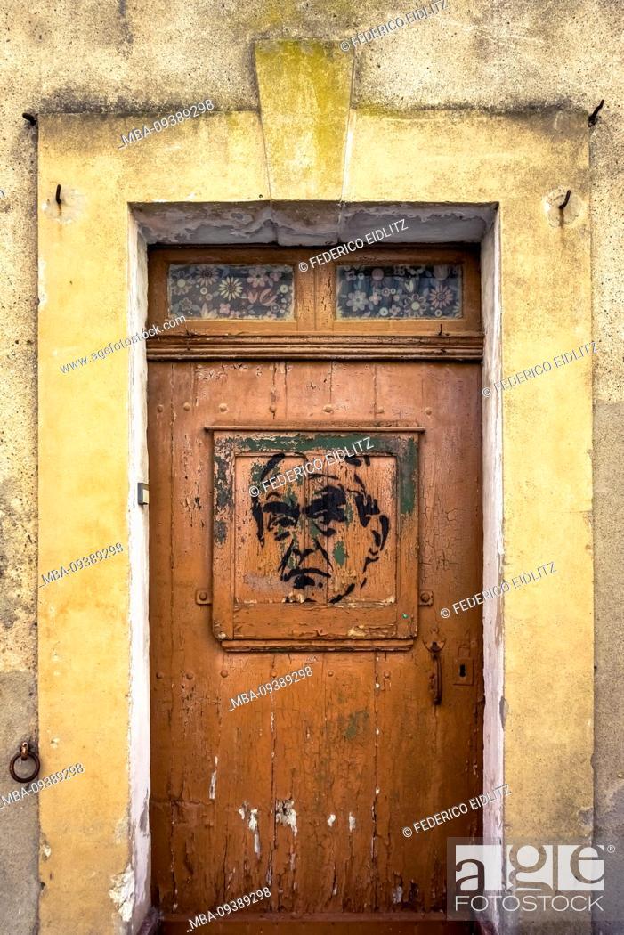 Stock Photo: Wooden door with graffiti in Nissan lez Enserune.