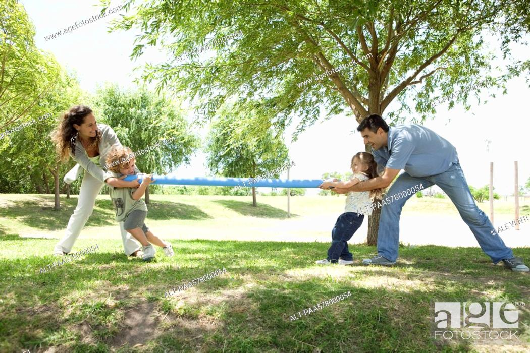 Stock Photo: Family playing tug-of-war in park.
