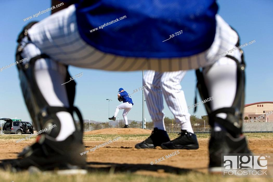 Stock Photo: Baseball batter facing pitcher during competitive game, view through catcherÔÇÖs legs, rear view, focus on background.
