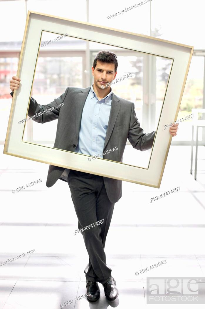 Stock Photo: Businessman holding a frame in an office lobby.