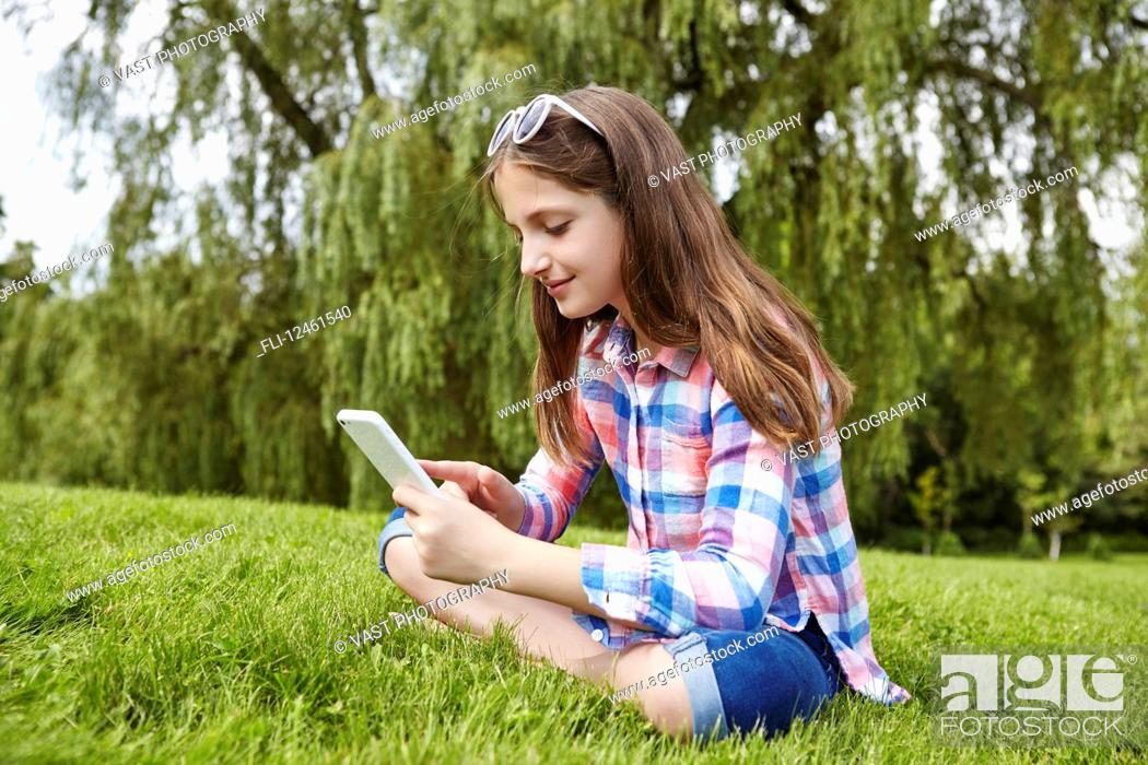 Imagen: Preteen girl sitting in a park holding a tablet; Toronto, Ontario, Canada.