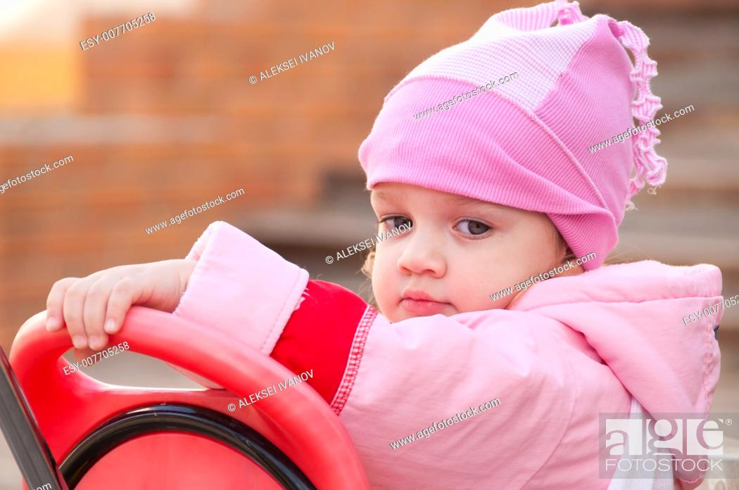 Stock Photo: Two-year-old girl sitting on children Bicycle and thoughtfully looks down.