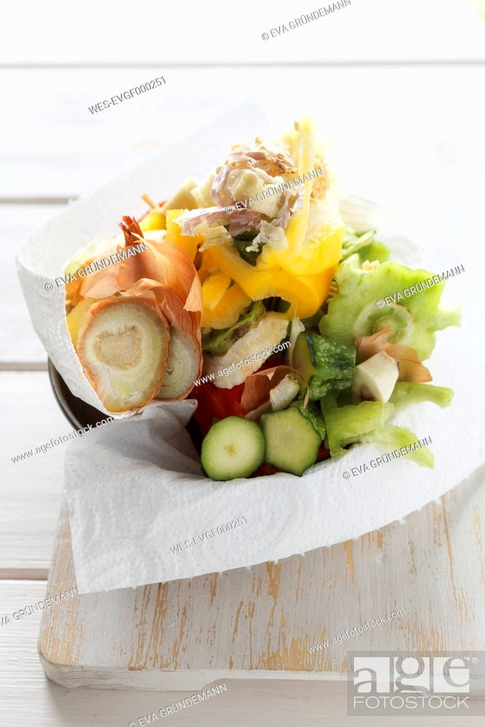Stock Photo: Organic waste of different vegetables wrapped in kitchen paper on chopping board, studio shot.