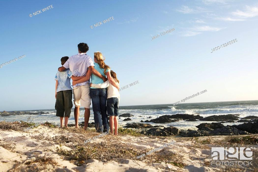 Stock Photo: Family standing together on beach back view.
