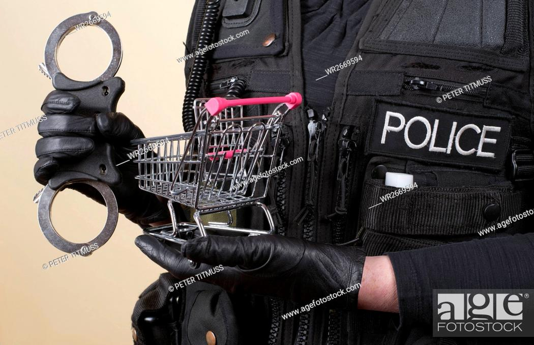 Stock Photo: Police officer holding handcuffs and supermarket trolley in concept of shoplifting.
