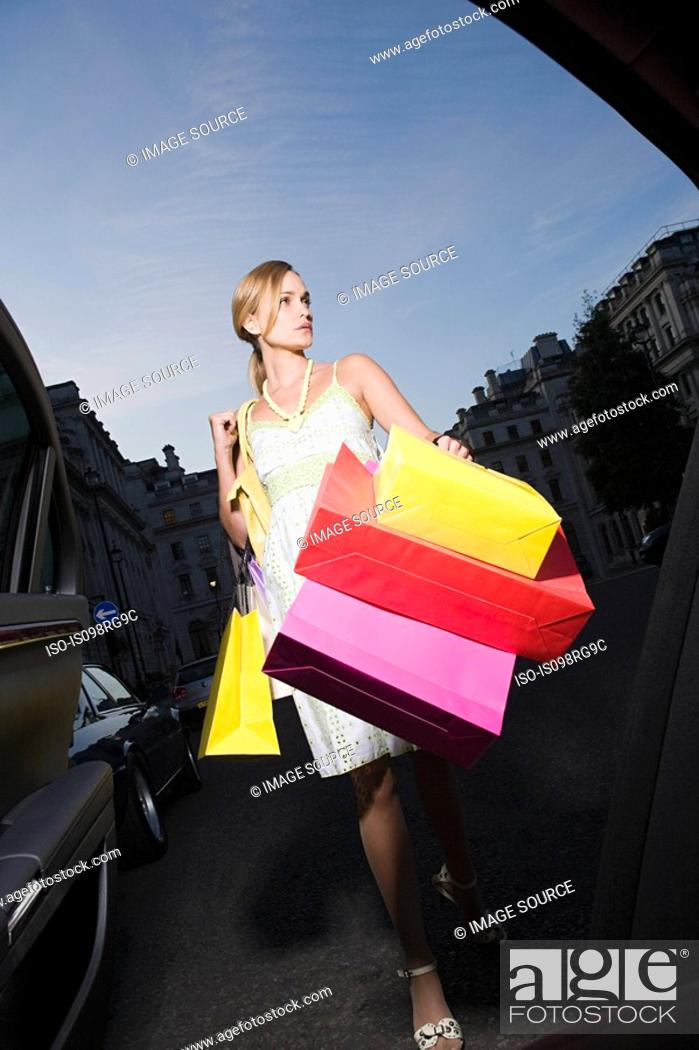 Stock Photo: Young woman carrying shopping bags.