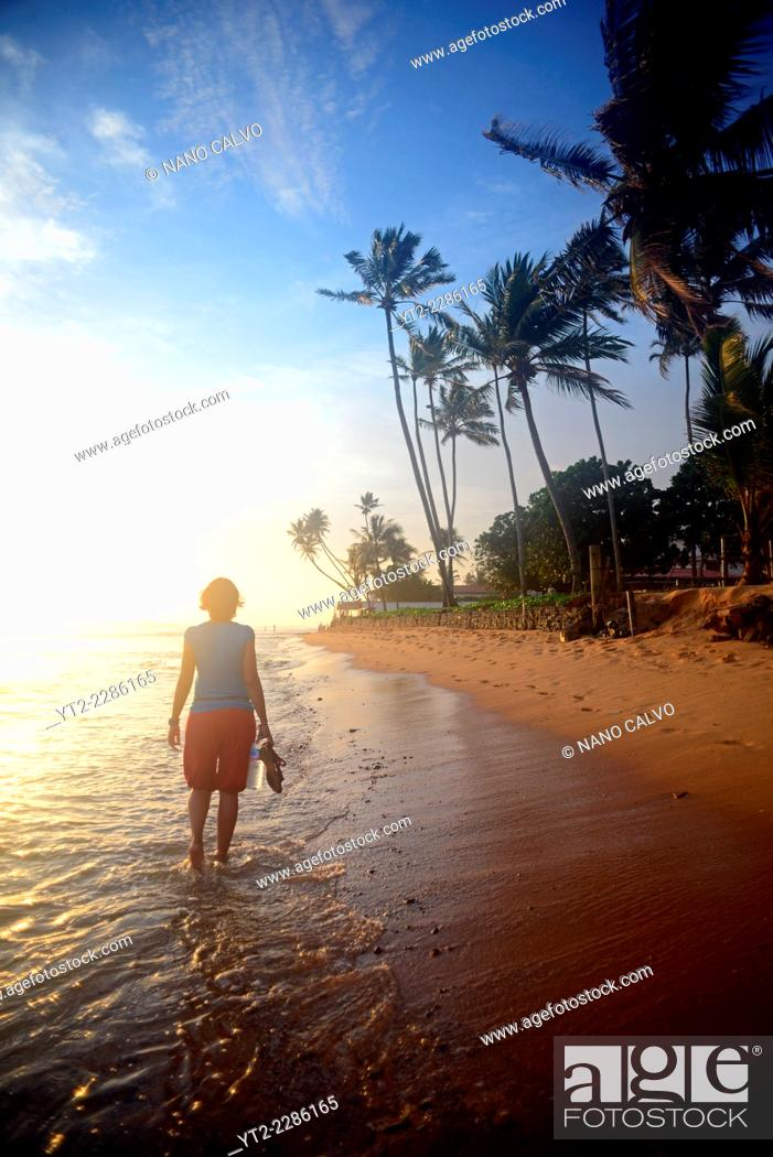 Stock Photo: Young woman walking on Hikkaduwa beach at sunset, Sri Lanka.