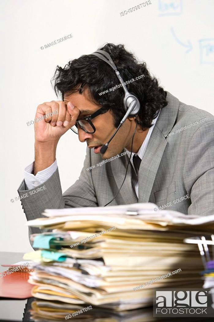 Stock Photo: Stressed businessman with head in hands.