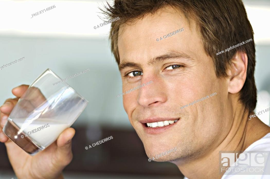 Stock Photo: Portrait of young man drinking milk.