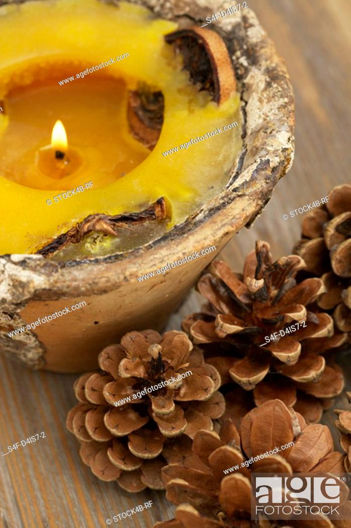 Stock Photo: Perfumed candle and pine cones.