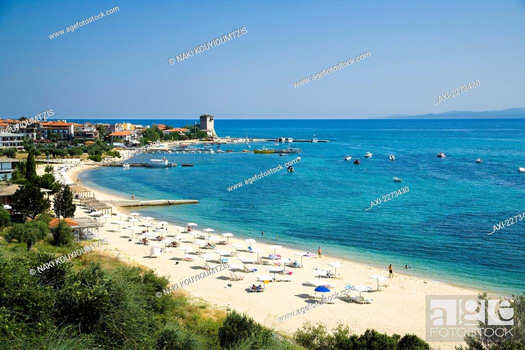 Imagen: Greece, Halkidiki, Tower of Prosforios in the distance; Ouranoupoli, Tourist beach with beach umbrellas and sun bathers with Byzantine tower.
