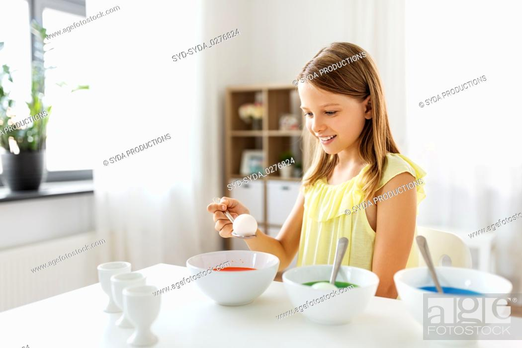 Stock Photo: girl coloring easter eggs by liquid dye at home.
