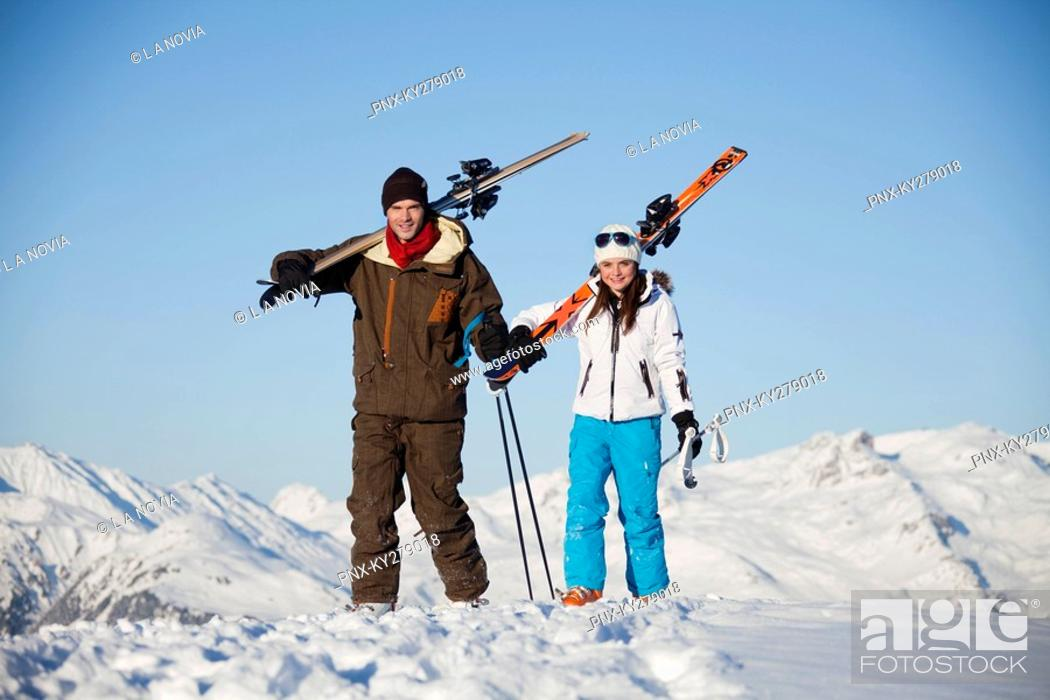 Stock Photo: Father and daughter carrying skis.