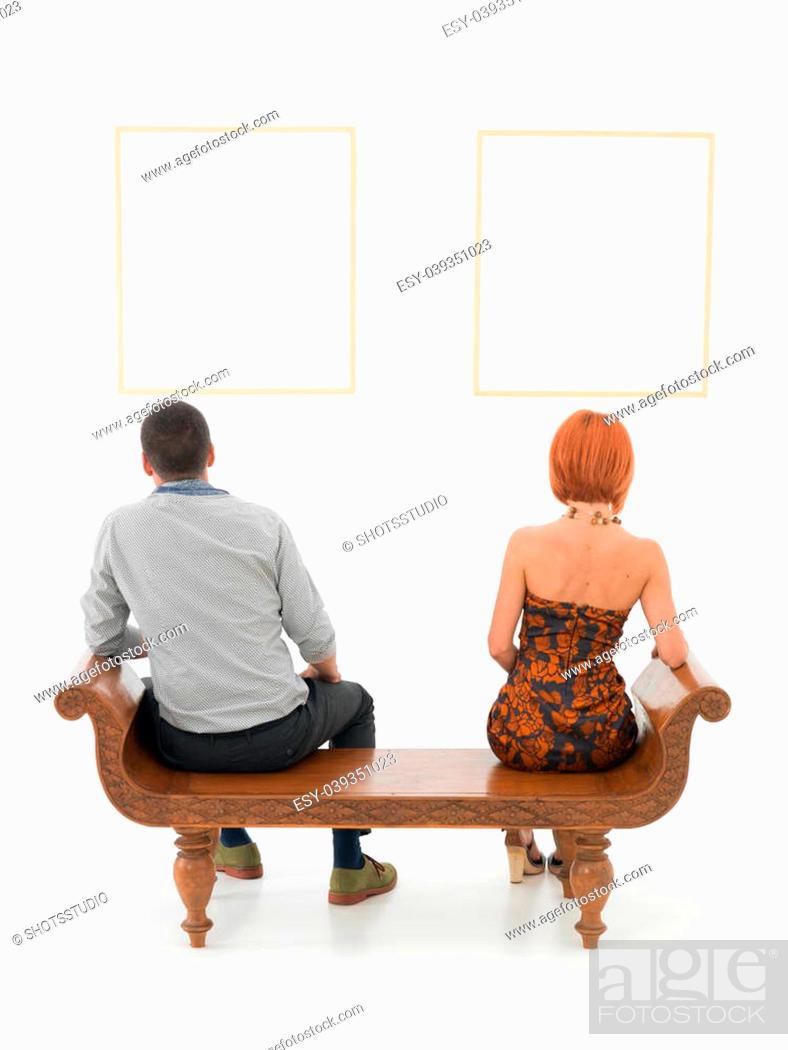 Imagen: rear view of man an woman sitting on a wooden bench looking at empty frames displayed on a white wall in front of them.