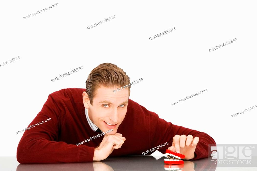 Stock Photo: Portrait of a businessman with dentures on a table.