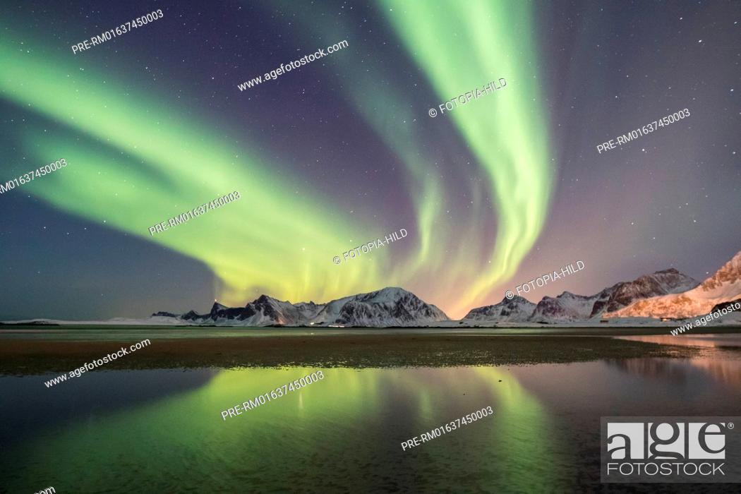 Stock Photo: Aurora borealis north of Yttersand, Moskenesøya, Lofoten, Nordland, Norway, March 2017, looking northeast over the Vareidsundet to Vareid with the mountains.